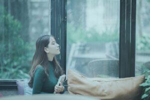 女性 窓 雨