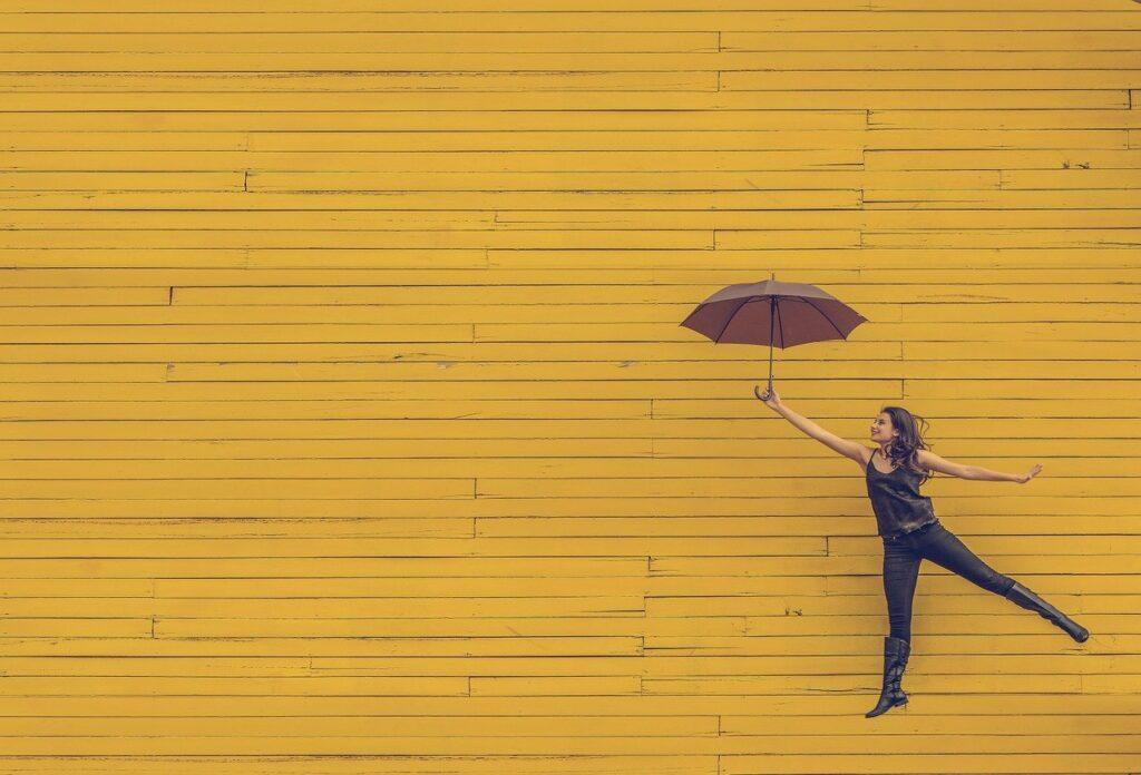 女性 傘 黄色い壁